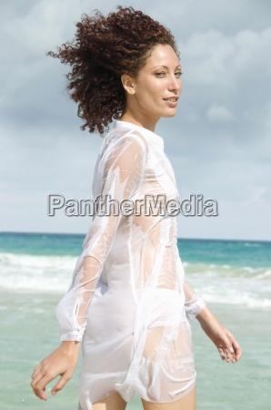 young woman walking in ocean side