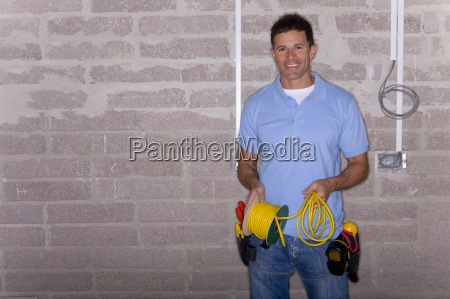 smiling electrician holding cable