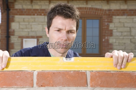 close up of bricklayer using level