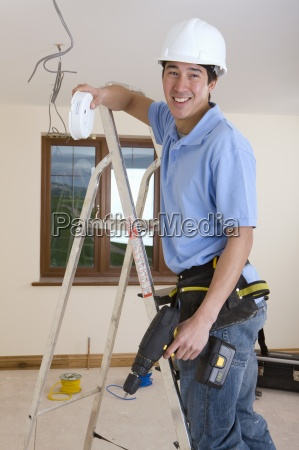electrician on ladder holding smoke detector
