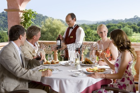 waiter presenting wine to well dressed