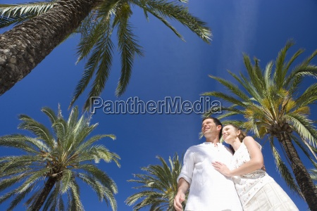 smiling couple hugging under palm trees