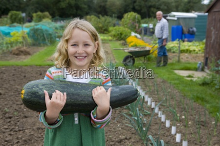 girl holding large squash