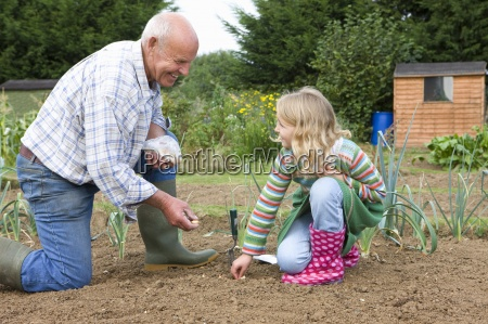 man and granddaughter planting seeds
