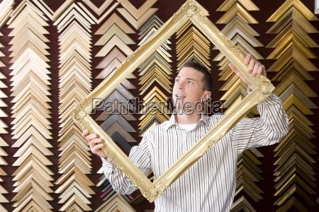 clerk lifting gold frame in frame