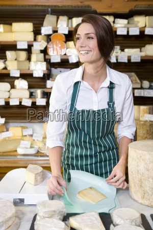 saleswoman standing at counter wrapping wedge