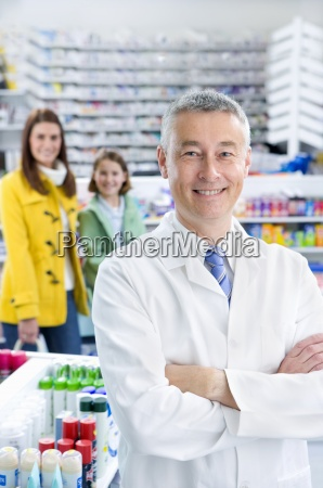 pharmacist in pharmacy with customers in