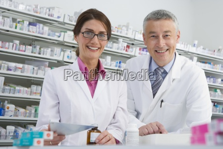 pharmacists filling bottle with medicine in