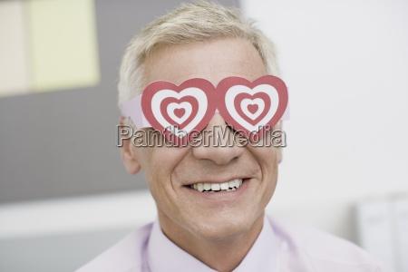 a mature businessman wearing paper heart