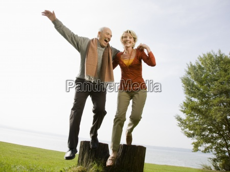 a senior couple jumping off a