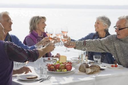 five senior friends having lunch raising
