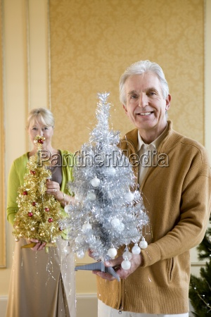 senior couple with ornamental christmas trees