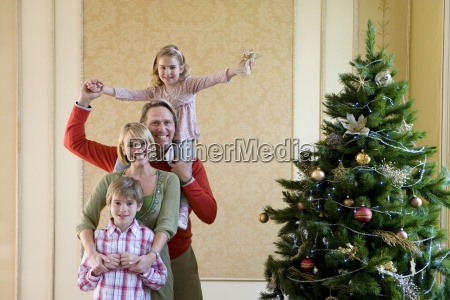 family of four by christmas tree