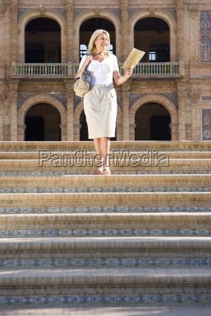 senior woman with tourist map descending