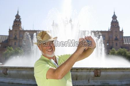 senior man taking photograph by fountain