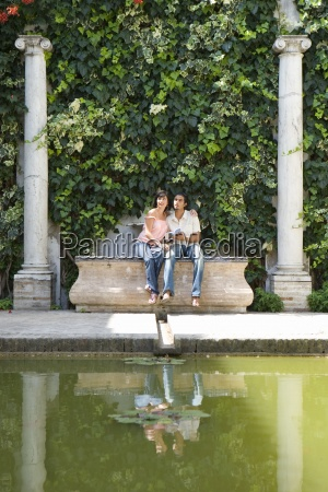 young couple sitting by pond reflection