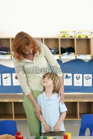 boy 4 6 and teacher standing