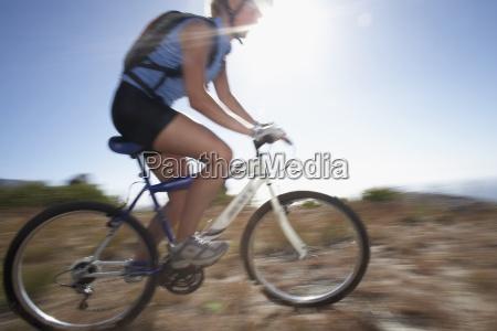 mountain biker cycling across extreme terrain