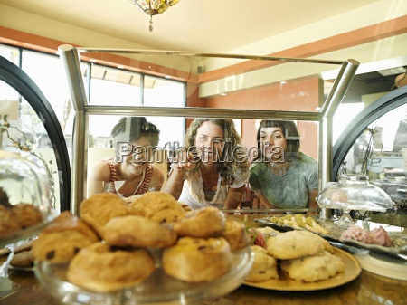 three young women staring at pastries