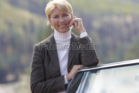mature woman standing beside car smiling