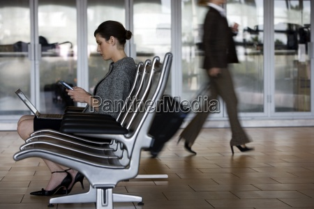 businesswoman sitting in waiting area using