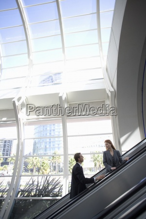 businesswoman and businessman ascending escalator side