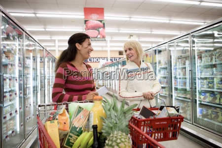 two women shopping in supermarket standing