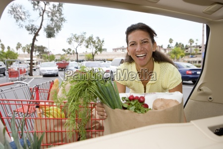 woman loading car with grocery bags