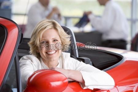salesman with customer in car showroom
