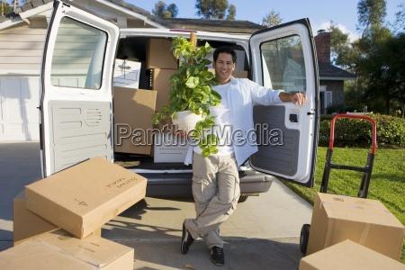 man moving house standing beside van
