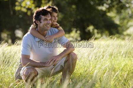 man crouching in woodland field son