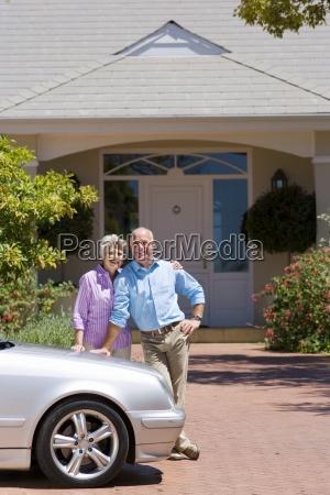 senior couple standing beside parked car