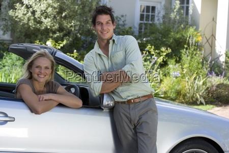 couple posing on driveway man standing