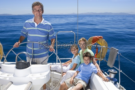 family relaxing on deck of sailing