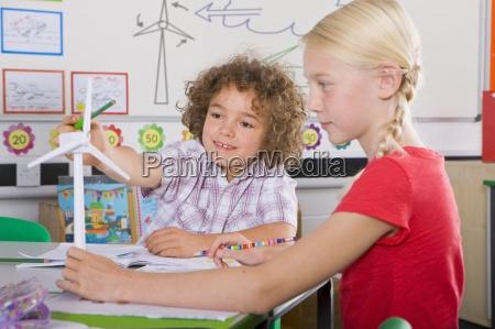 curious students examining model wind turbine