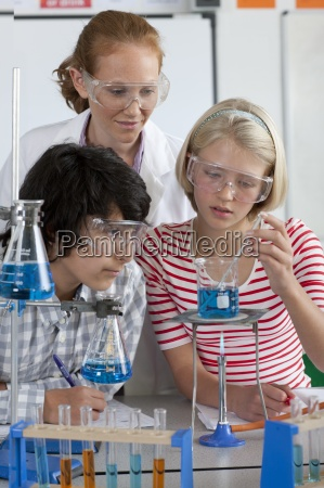 teacher watching students performing experiment in