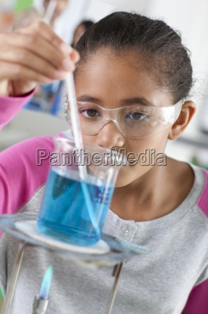 student performing experiment in school chemistry