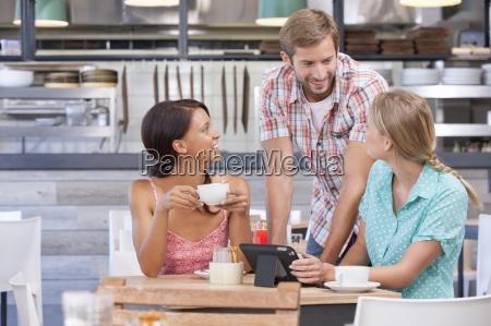 friends using digital tablet in coffee