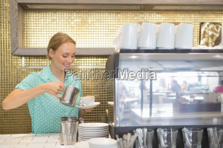 smiling waitress pouring cup of coffee