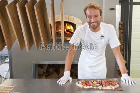 smiling chef preparing pizza in kitchen