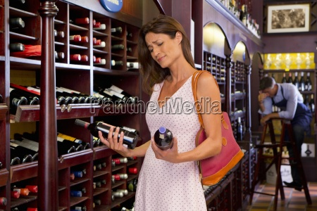 frustrated customer examining bottles in wine