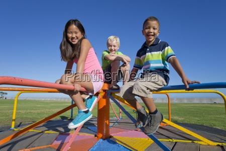 smiling children sitting on carousel in