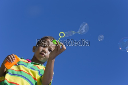 boy blowing bubbles with bubble wand
