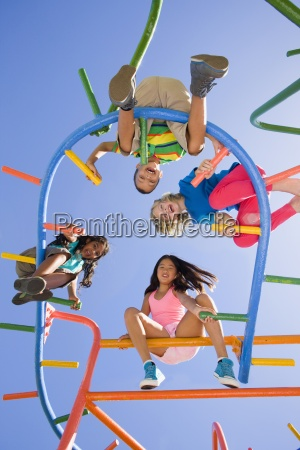 children sitting on monkey bars at