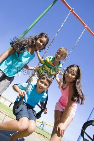 children smiling together at swing set