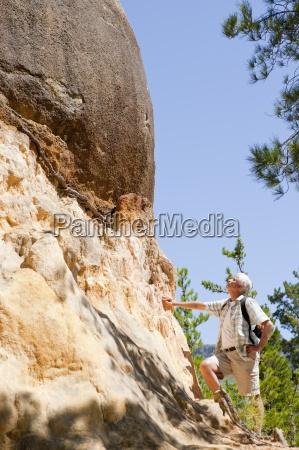older man admiring rock formation on