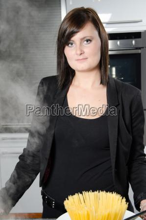 young woman cooks spaghetti