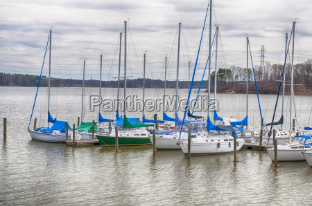 parked yachts in harbour with cloudy