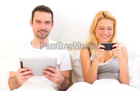 young attractive couple using mobile and