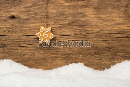 hanging gingerbread with snow on wood